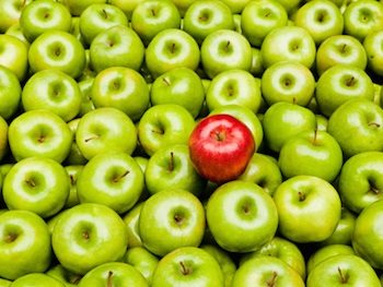 This picture shows a bushel of green apples and one red apple, which highlights the anomaly in the bunch.